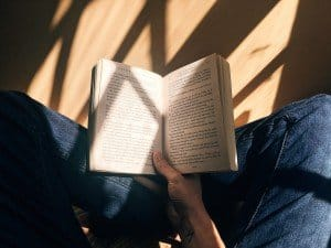 Fille avec un livre, par terre