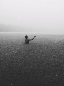 Une femme au milieu de l'eau dans la brume, noir et blanc