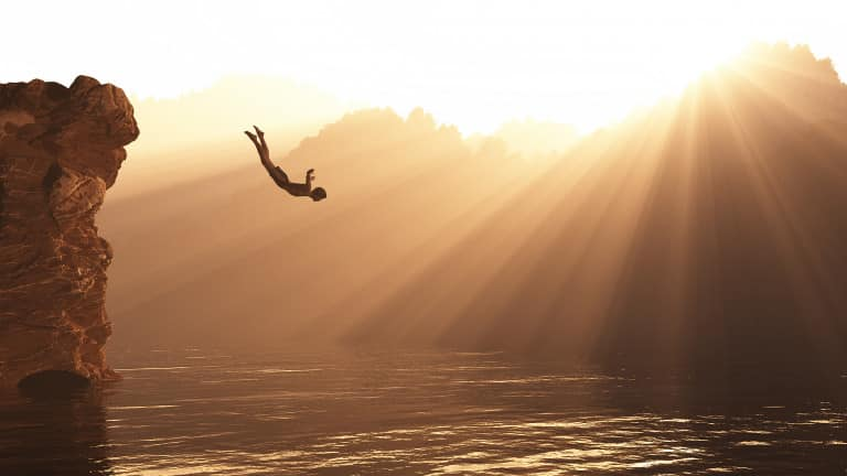 Personne sautant depuis une falaise pour plonger, sous le soleil de la Golden Hour