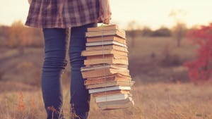 Personne tenant des livres dans la nature