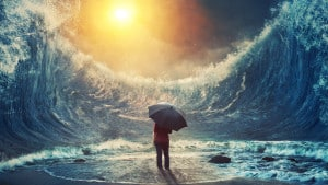 Une personne tenant un parapluie face à de gigantesques vagues